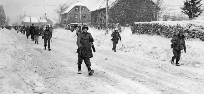 Soldiers of the Big Red One enter snowy Butgenbach, Belgium, on Christmas Eve—the day Puhalovich rejoined his unit after being wounded in the Hürtgen Forest the previous month.