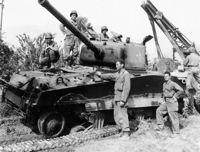 Crewmen of a damaged M4 Sherman medium tank belonging to the U.S. 1st Armored Division await the attachment of towing equipment from a recovery vehicle in the background of this photo. The tank was immobilized during the fighting around Cisterna in May 1944.