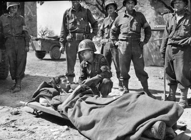 """An American medic provides a drink of water to a wounded German prisoner somewhere in Italy. """"Commando"""" Charles E. Kelly was a one-man destructive force in combat against the Germans, and this soldier may have been one of the casualties he inflicted on the enemy."""