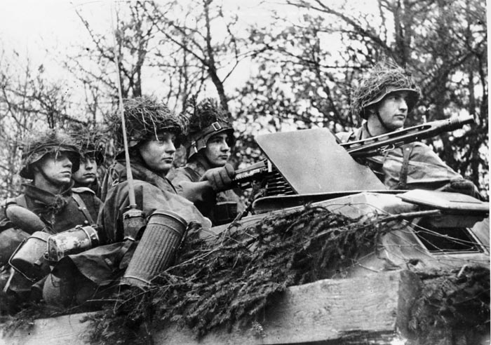 Well-camouflaged German soldiers advance in a light infantry fighting vehicle through Belgium during the Battle of the Bulge. American tanks, tank destroyers, and armored infantry of Team Desobry held off the German 2nd Panzer Division for a day until paratroopers from the 101st Airborne Division joined the fight. The Siege of Bastogne would last for eight days.