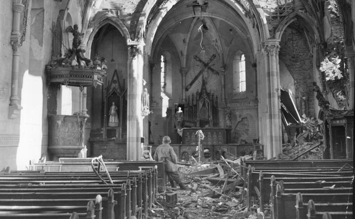 An American soldier surveys Noville's wrecked church. Twice, members of Team Desobry took the church's spire under fire, once to kill a sniper and again to collapse the tower in hopes the resulting debris would block the German advance.