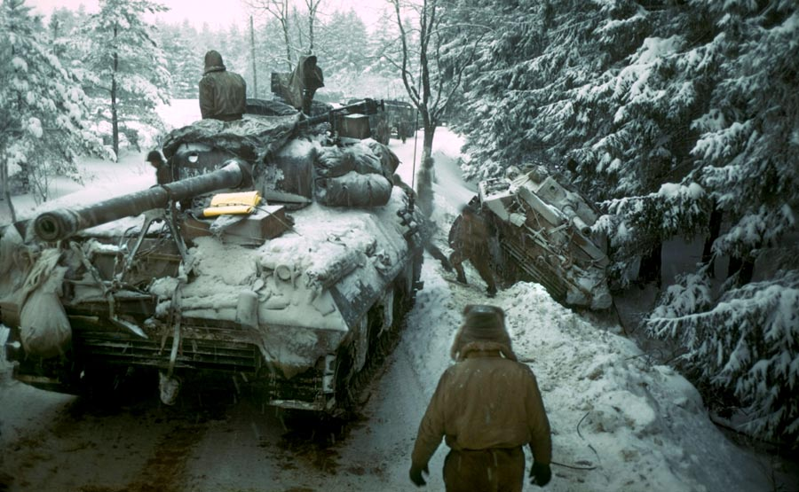 An American tank destroyer rolls past a disabled tank destroyer on a snow-covered road in Belgium. Tank destroyers from two different units helped Noville's defenders deny the Germans entry. No snow fell on Noville during the two-day battle, but the temperatures were cold.