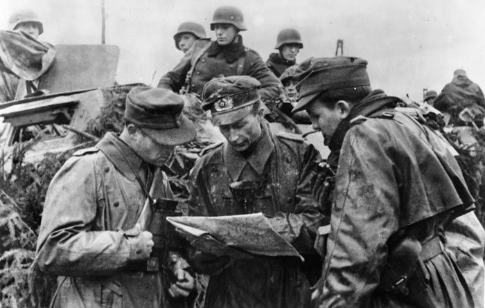 German officers confer over a map during the initial days of the Ardennes campaign. The Americans in Noville managed to kill or wound most of the German armor's support infantry. Without infantry, the tanks continually pulled back.