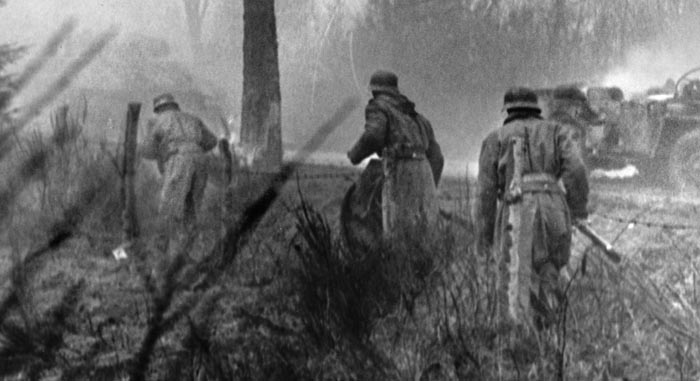 German soldiers advance along a raised road though Belgium's thick fog. The knocked-out American vehicles in the background are barely visible. Thick fog made fighting difficult for the Germans in Noville, while the Americans took advantage of it to hide their small numbers and eventually pull out of the village and head south.