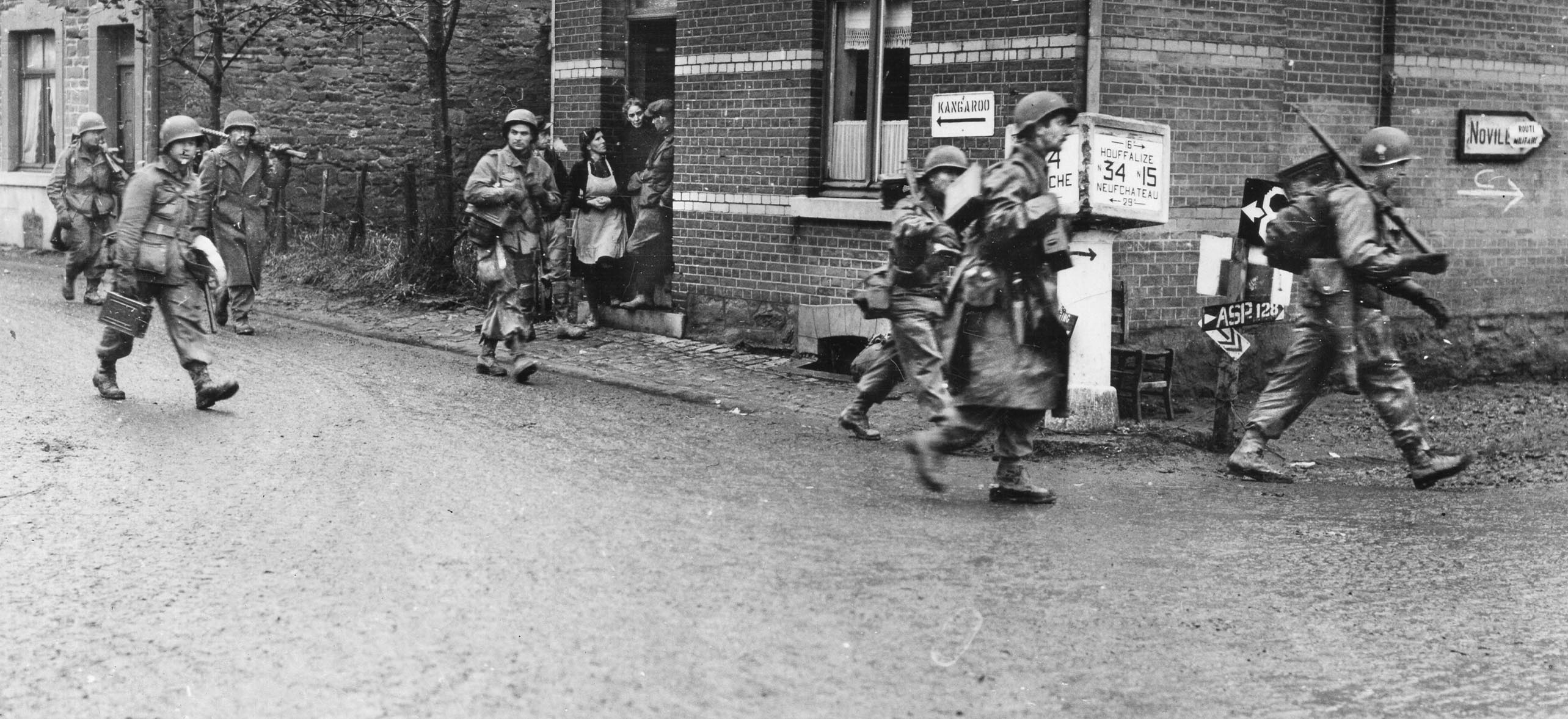 American paratroopers of Colonel Robert Sink's 506th Parachute Infantry Regiment, 101st Airborne Division pass through Bastogne. Sink's 1st Battalion, under Lt. Col. James LaPrade, headed north to help Team Desobry defend Noville.