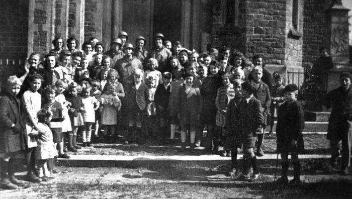 Local Noville civilians and children gather with their American liberators in front of the village church. After the Germans retook Noville, they found photographs like this and used them to round up civilians, including a Catholic priest, and kill them.