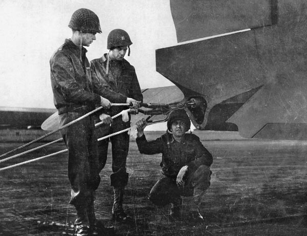 C-47 crew members inspect tow ropes on their plane