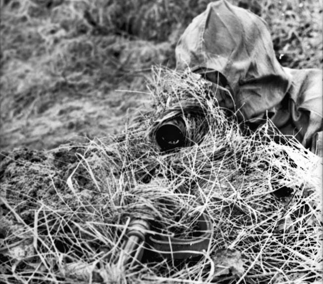 Somewhere in France a well-camouflaged German sniper peers through the scope of his rifle. Sepp Allerberger modified an umbrella to hold brush collected on site to hide his position.