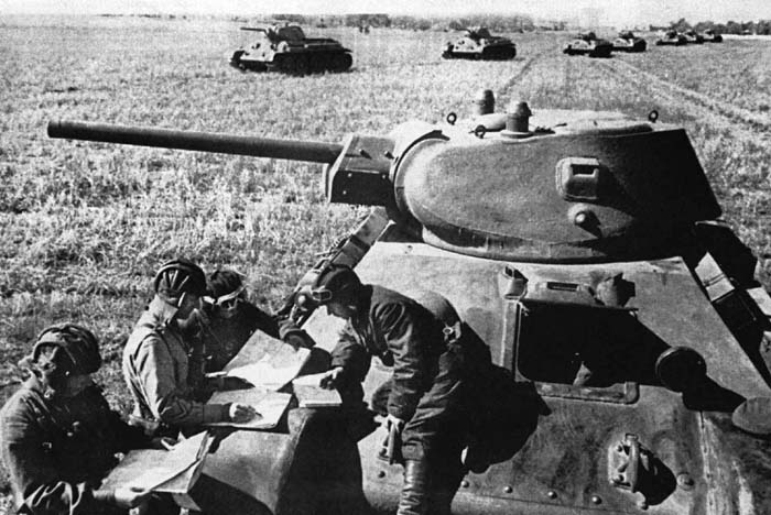 A Red Army tank crew studies maps on the hull of their tank as a line of T-34s passes to their rear. Some historians credit the T-34 tank as being responsible for the Allied victory over the Germans.