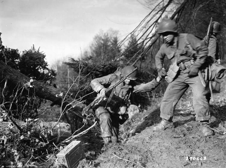 During the bloody Battle of Hürtgen Forest on November 18, 1944, Pfc. Benny Barrow of the U.S. 4th Infantry Division helps a fellow soldier to negotiate a difficult climb.