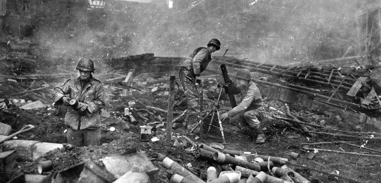During a fight to ward off a German counterattack at Grosshau on December 1, 1944, American soldiers of the 22nd Infantry Regiment man an 81mm mortar as fire is directed against the advancing enemy from a position amid the rubble of the village.