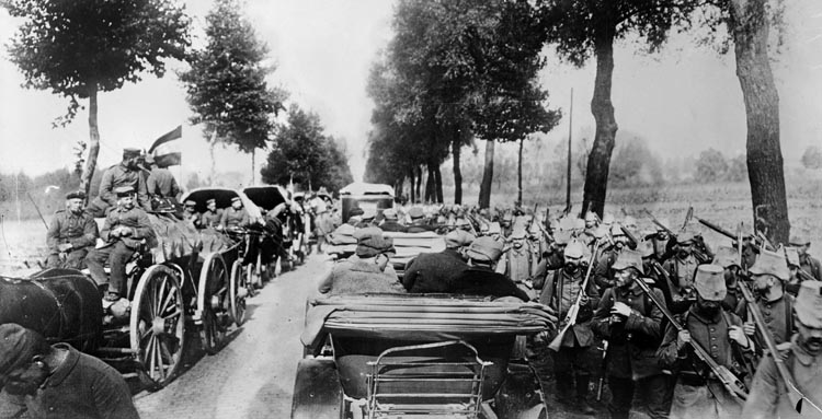 Germans marching into Belgium pass by Belgian refugees fleeing the fighting.