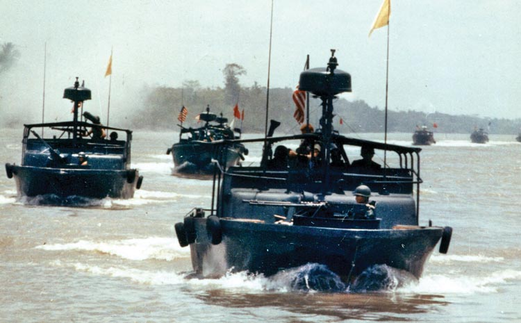 A flotilla of Navy PBRs fires on enemy positions during Operation Bold Dragon III in March 1969. PBRs were capable of delivering Navy SEAL teams and other ground troops to remote locations in the Mekong Delta.