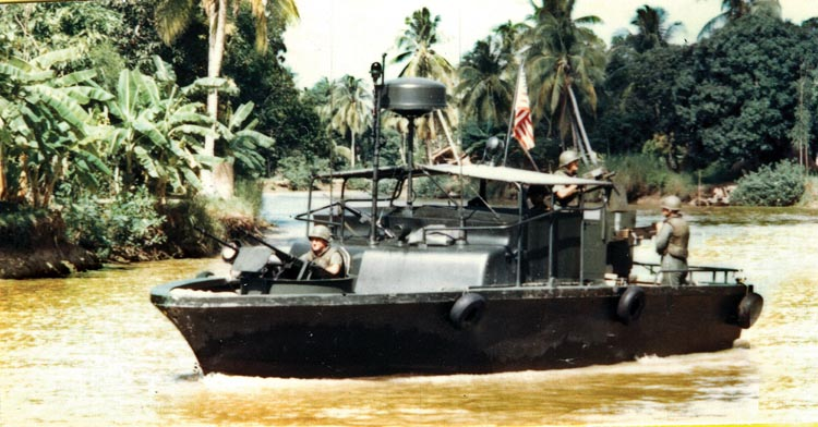 Crewman aboard a fiberglass-hulled Mark II River Patrol Boat watch closely for enemy activity during a mission in the Mekong Delta. Navy PBRs worked together with helicopters and ground units to interdict the flow of enemy troops and supplies on rivers and canals.