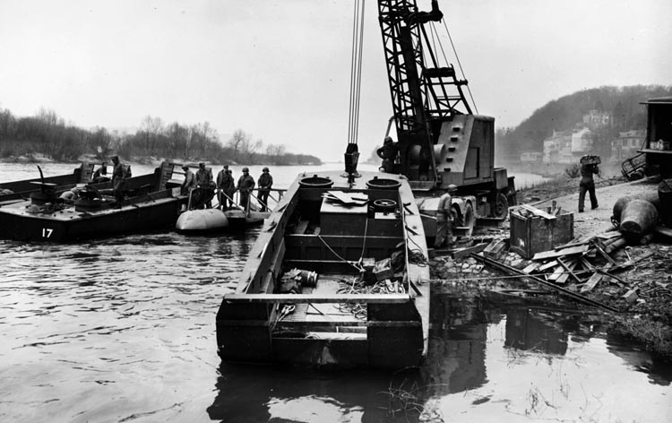 A crane lifts an LCVP (Landing Craft, Vehicle and Personnel)) into position prior to crossing the Rhine.