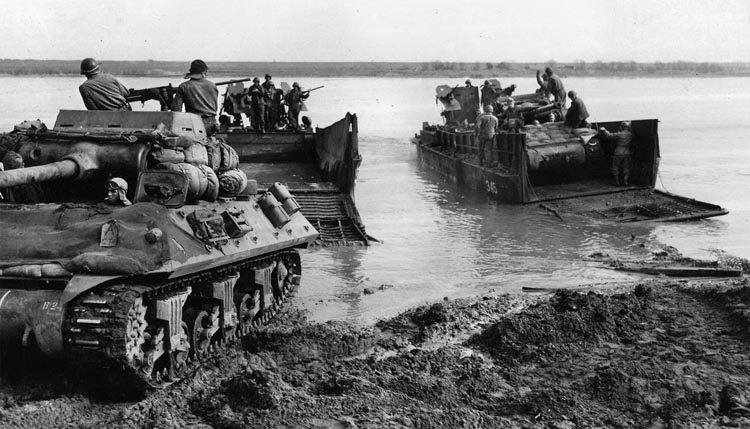 Two M-36 tank destroyers from a U.S. Ninth Army unit roll onto U.S. Navy LCMs (Landing Craft, Mechanized) in preparation for an assault crossing. Such large craft had to be transported to the river on tank-retriever trailers.