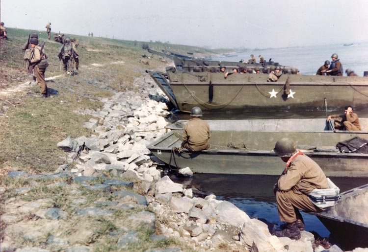A rare color photograph shows 79th Infantry Division troops preparing to cross the river at Orsoy, Germany, north of Duisburg, March 10, 1945. The boats in the foreground are bridge pontoons.