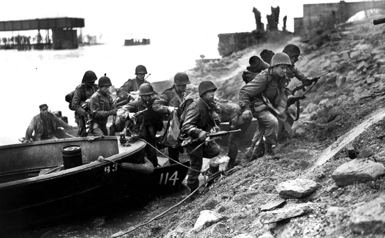 Men of the U.S. 7th Army scramble from their assault boat and head up the muddy eastern bank of the Rhine River near Frankenthal, March 26, 1945, one day after the Battle of Remagen.