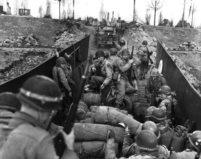 "80th Infantry Division soldiers and vehicles of Patton's Third Army load into a landing craft prior to a Rhine crossing ""somewhere in Germany."""