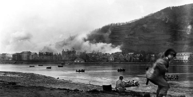 Smoke rising from St. Goarhausen screens the enemy's view of assault boats carrying troops crossing the Rhine, March 26, 1945.