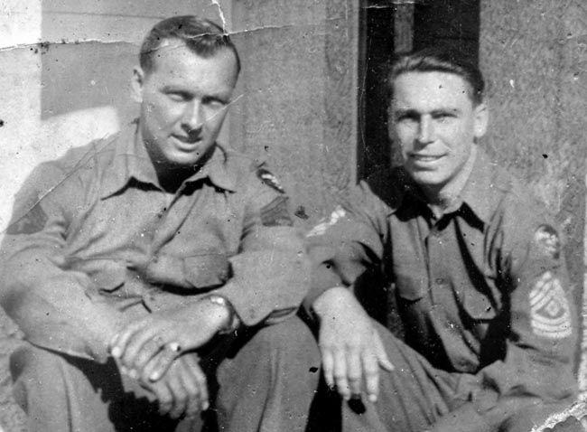 Technical Sergeant Tony Sorgent (left) relaxes with First Sergeant Joe Cotten. Sorgent constantly scrounged for food and made meals for the men in Cotten's company.