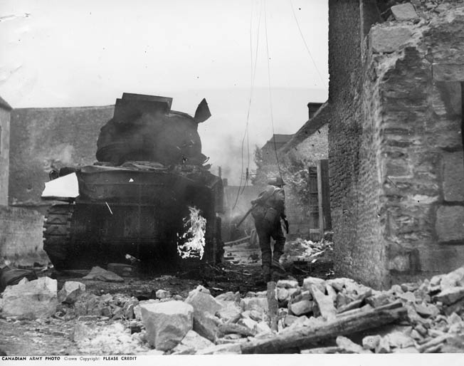 A Canadian soldier dashes past a disabled Sherman tank whose rubber track pads are on fire.