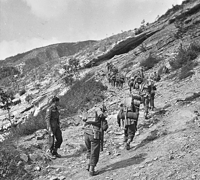 Troops of the 1st British Infantry Division, attached to the Fifth Army, advance up a steep mountain trail near Monte Pratene, September 1944.