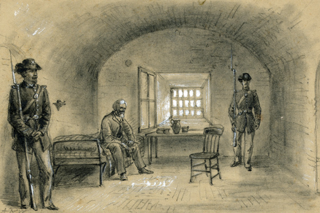 A weary and suddenly aged Jefferson Davis sits in chains under guard in his cell at Fort Monroe. He was released on bond two years later by President Andrew Johnson.
