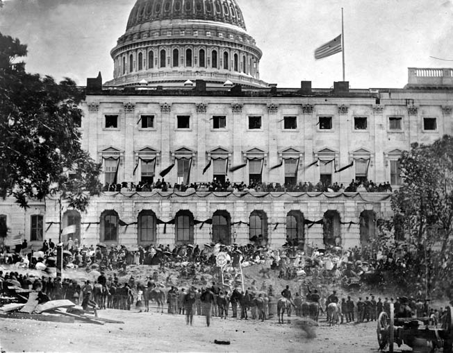 Spectators line Pennsylvania Avenue in front of the Capitol building, which still flies the American flag at half-mast in honor of the assassinated President Lincoln.