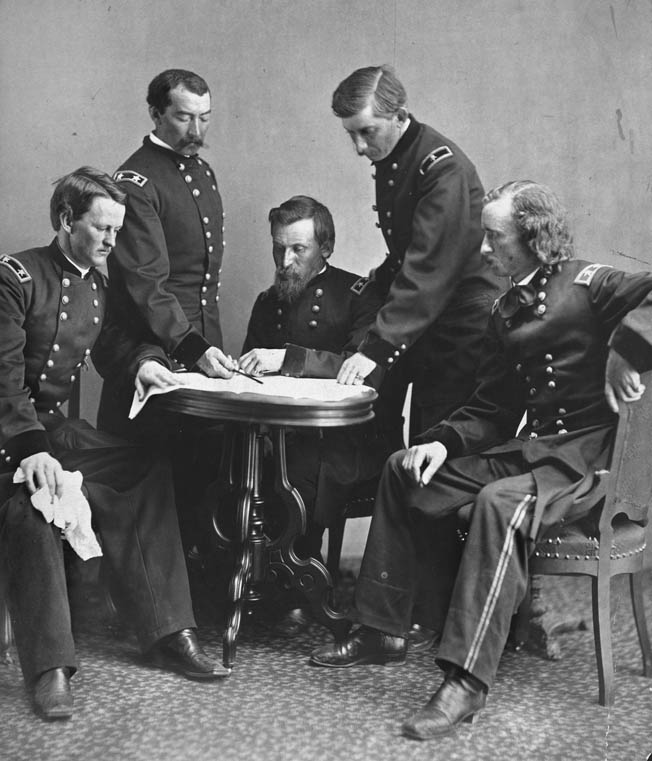 Maj. Gen. Philip Sheridan, second from left, peruses battle plans with members of his general staff. The others, left to right, are Wesley Merritt, George Crook, James Forsyth, and George Armstrong Custer.