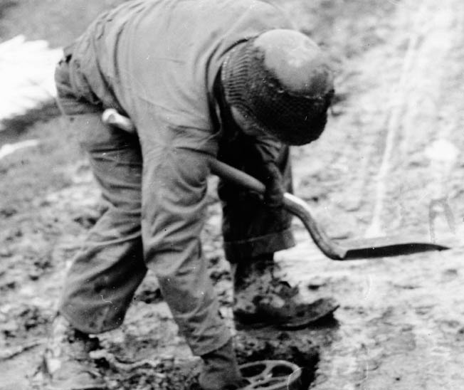 Several days after the fighting at the Wahlerscheid Crossroads has ended, an engineer of the 2nd Infantry Division plants a mine. The GIs were preparing strong defenses as the Battle of the Bulge raged nearby.