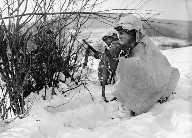 Keeping a sharp watch for enemy troop movement, two soldiers of the 2nd Infantry Division man a forward position along a ridge in Belgium. The soldier in the foreground is wearing winter camouflage that he appears to have put together on his own with bedsheets or large pieces of canvas.