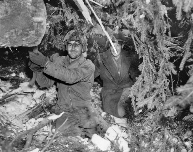 A pair of American soldiers from the 38th Regiment of the 2nd Infantry Division smile for the camera but work quickly to prepare a bazooka position as they lie in wait to defend ground around the embattled Wahlerscheid Crossroads.