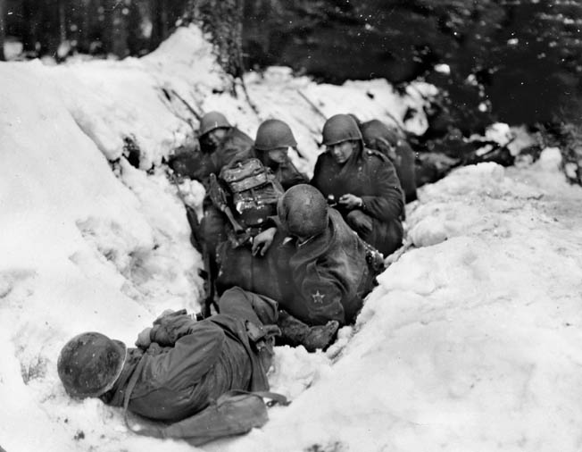 On the afternoon of December 14, 1944, soldiers of the 9th Infantry Regiment, 2nd Division hug the snowy ground on the side of a ditch. The 9th Infantry was heavily engaged during the battle for the Wahlerscheid Crossroads, which the soldiers of the 2nd Division nicknamed Heartbreak Crossroads.