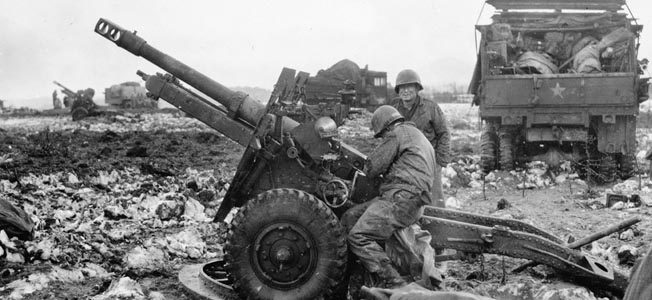 Operating a British-made QF 25-pounder field gun, American artillerymen of the 2nd Infantry Division prepare to fire in support of attempts to secure the Wahlerscheid Crossroads from the Germans. The truck at the right appears to hold their gear.