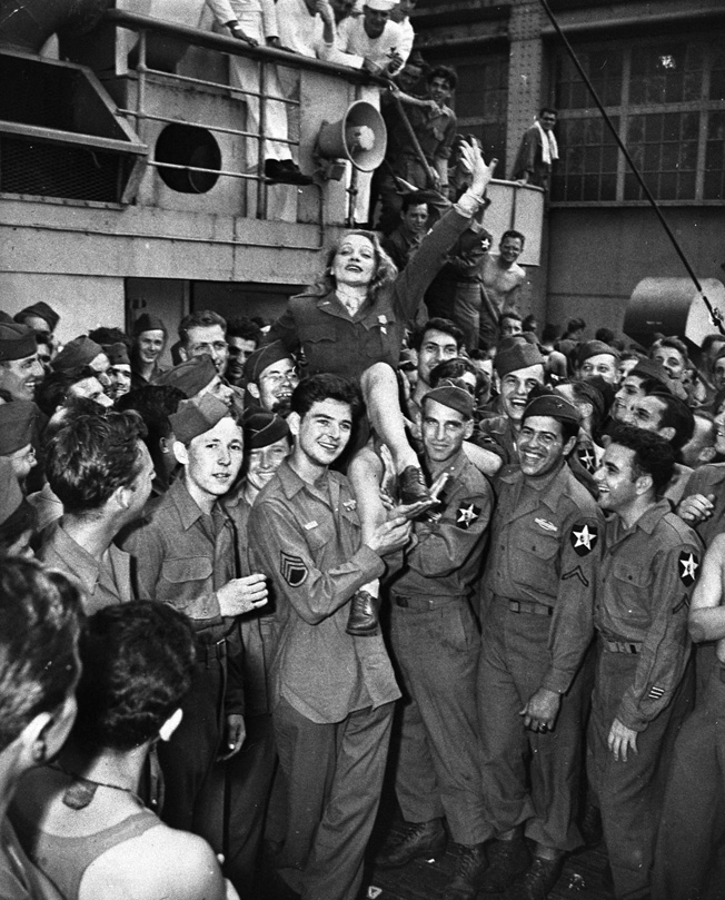 Marlene Dietrich is hoisted onto the shoulders of 2nd Infantry Division soldiers on the troopship SS Monticello as they return to New York Harbor at war's end. General Patton once gave her a pistol for protection in the event she was ever captured by the Nazis.