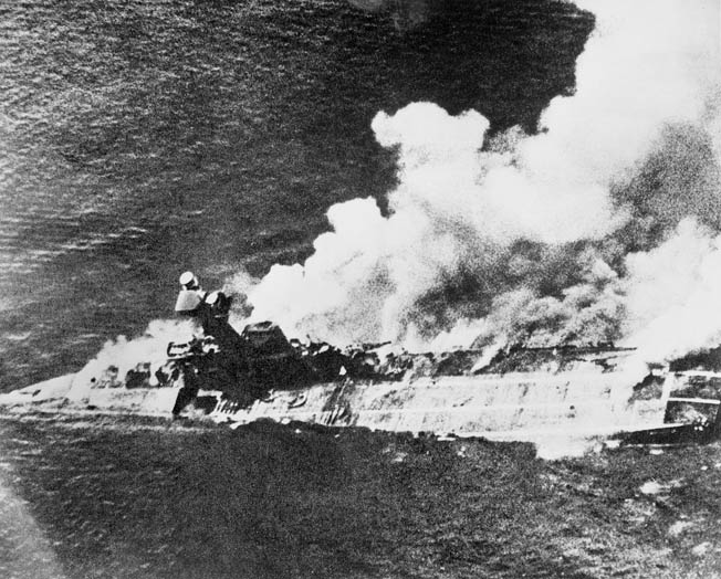 After sustaining more than 40 direct hits from Japanese bombs, the British aircraft carrier Hermes burns furiously. Her forward elevator has been blown out of its well, and smoke billows from deep inside the ship. The carrier sank in 20 minutes with the loss of 18 officers and 288 sailors.