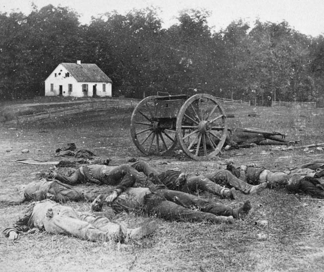 Slain Union infantry and Confederate artillerymen lie together on the field in front of Dunker Church. It would be the bloodiest single day in American history.