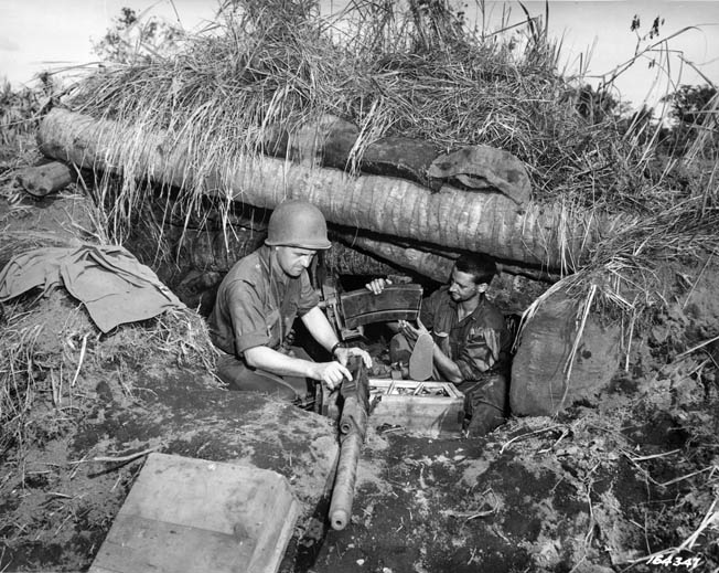 Soldiers of the 32nd Infantry Division maintain their machine gun from a reinforced position in the New Guinea jungle. American firepower and supply gave them a decided advantage in the upcoming fight at the Driniumor River.