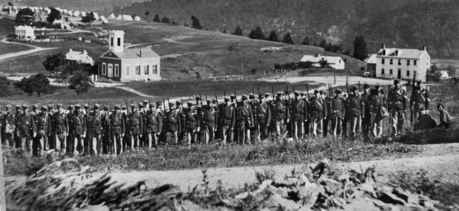 Company A, 22nd New York State Militia, poses for a group photograph near Harpers Ferry. Confederate forces would later seize the arsenal.
