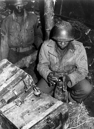 An artilleryman of the 333rd sets the fuse of a 155mm round near Schlausenbach, Germany, October 1944.