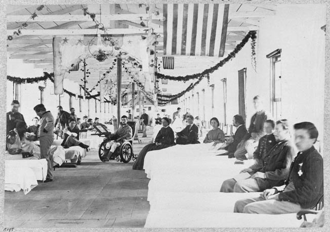 Ward K, Armory Square Hospital, Washington, D.C., sports flags and holiday greenery, giving it a festive appearance totally at odds with the grim reality of war and wounds.