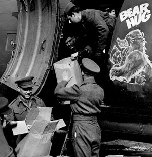 Bear Hug, a Troop Carrier Command C-47, is loaded with rations, cartons of cigarettes, and candy to be donated to former Russian POWs waiting to return home.