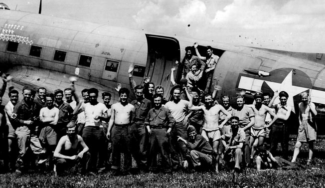 U.S. and British POWs stand in front of their C-47 near their prison camp, Stalag VII-A in Moosburg, Germany, prior to boarding for their return flight.