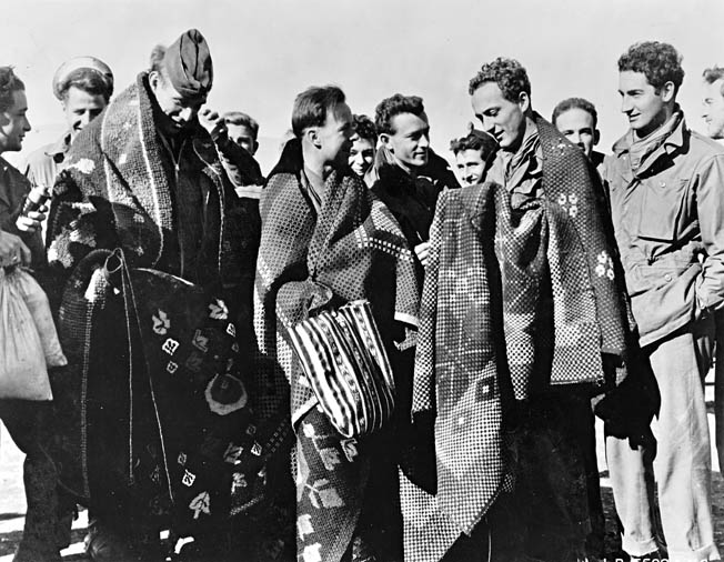 Crewmen from a downed aircraft of the Fifteenth Air Force escaped capture with the help of Yugoslav partisans. Here they arrive in Italy wearing Yugoslav blankets.