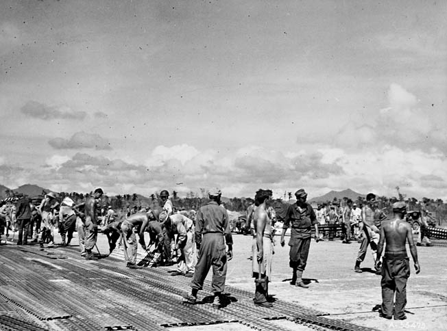 Combat engineers installing Marsden Matting, a perforated steel runway material. After landing on northern Leyte in October 1944, construction crews began building the Tacloban airstrip from which air attacks could be launched.