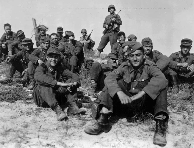 Dressed in uniforms issued by the German Army, members of the Russian Liberation Army sit under guard after their capture during the fighting in Normandy. Many of these men were returned to the Soviet Union after the war only to be executed.