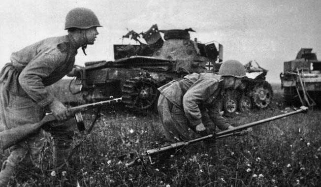 Red Army soldiers crouch as they attack past destroyed German tanks during the defense of the Kursk salient. The soldier on the right carries a heavy antitank rifle, which was woefully ineffective against heavily armored German tanks.