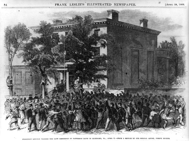 President Abraham Lincoln, accompanied by a throng of black and white supporters, enters the Confederate White House, where he would try out Jefferson Davis's former chair.