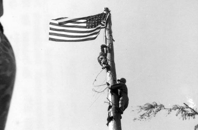 Raising their flag in triumph for the first time on Corregidor in three years, Americans T/5 Frank Guy Arrigo and Pfc. Clyde I. Bates climb the pole to secure the banner.